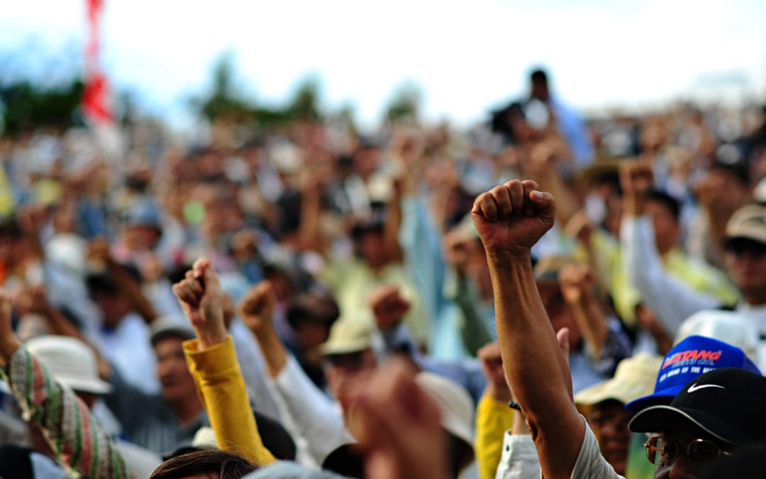 a crowd of people with raised fists
