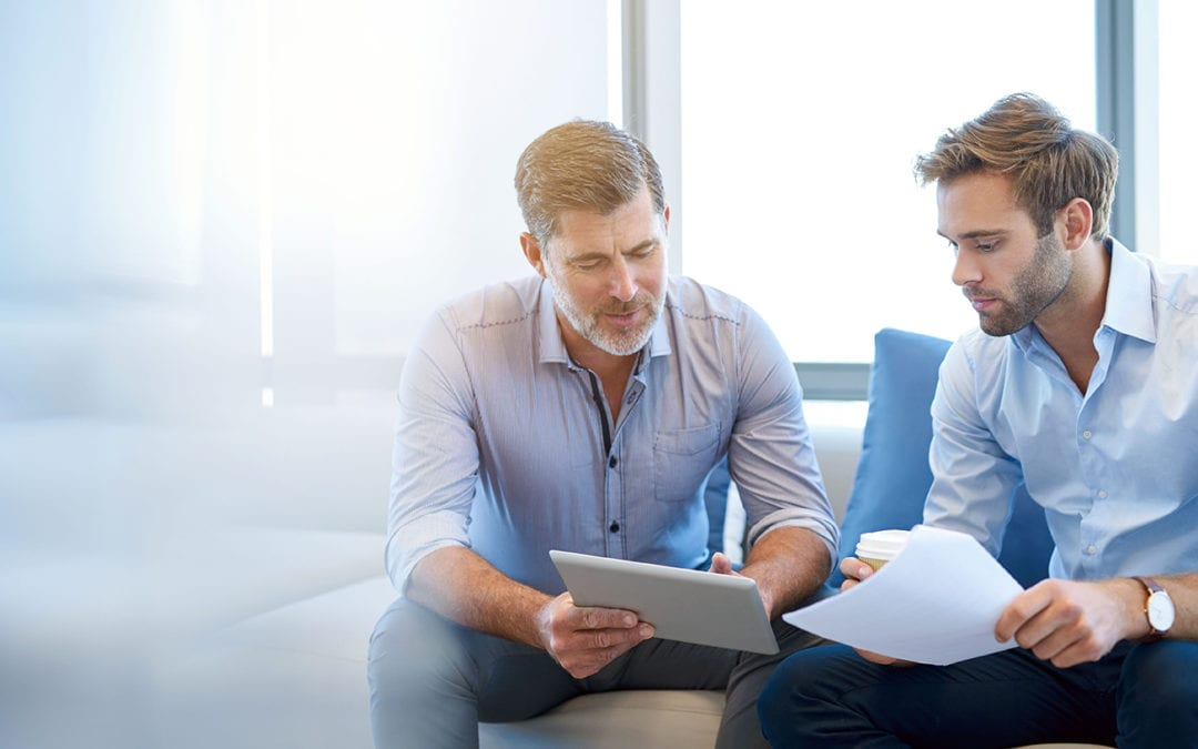 two businessmen discussing something displayed on an ipad