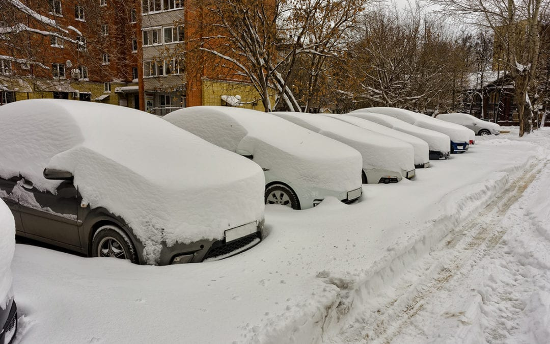 cars covered in snow in a parking lot