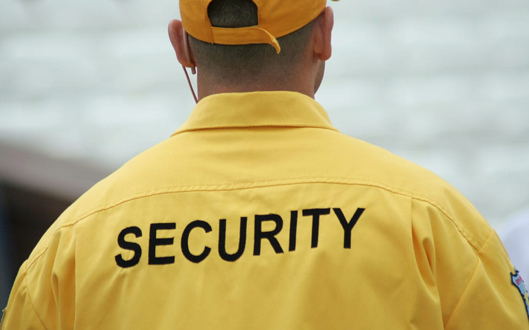 """a man wearing a jacket with """"security"""" on the back of it"""